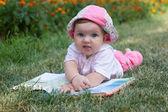 Pasgeboren baby lezen boek in park — Stockfoto