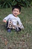 Happy asian boy sitting on a grass — Stock Photo