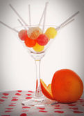 Orange and candys in a glass — Stock Photo