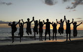Silhouette of friends jumping on beach during sunset time — Stock Photo