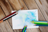 Colorpencils and brush on table — Stock Photo