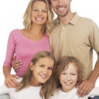 Happy caucasian family standing together and smiling happily — Stock Photo #26765077