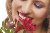 Closeup of face of young smiling woman with bunch of flowers — Stock Photo