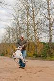 Man turning his dog around — Stock Photo