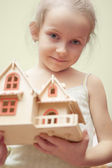 Little girl holding scale house model — Stock Photo