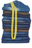 Plenty of male jeans in stack together with tape-line — Stock Photo