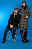 Man sitting on high chair with beautiful woman in coat — Stock Photo