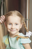 Portrait of a cute blond little girl being plait by mother — Stock Photo