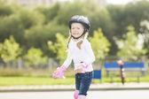 Gülümseyen sevimli sarışın beyaz kız bir yolda patinaj portresi — Stok fotoğraf