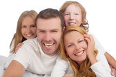 Family laughing together while laying on bed covered with white — Stock Photo