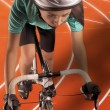 Постер, плакат: Professional female athlete riding bike on a track vertical sho