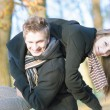 Funny caucasian young couple making piggyback together — Stock Photo