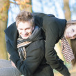 Funny caucasian young couple making piggyback together — Foto Stock