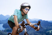 Portrait of young woman cycling over the mountains — Stock Photo