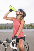 Cyclist woman takes a water break — Stock Photo