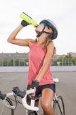 Cyclist woman takes a water break — Stock Photo