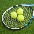 Tennis racket with three balls lies on a green lawn surface.  — Stock Photo