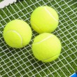 Three tennis balls lie on a tennis racket strings. — Stok fotoğraf
