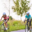 Two caucasian girlfriends riding bikes — Stok fotoğraf