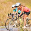 Two women exercising on bicycles outdoors. — Stock Photo #30515851