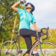 Young female cyclist athlete having a water break — Stock Photo