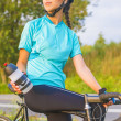 Cyclist athlete on bicycle having a water break. — Stock Photo