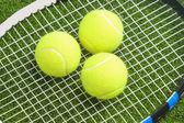 üç tenis topları, tenis raketi iplerde yalan. — Stok fotoğraf