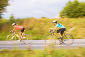 Two female caucasian sportswomen riding sport bikes outdoors — Stock Photo