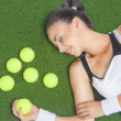 Stock Photo: Female Tennis Player Lying on Artificial Grass Surface With Tenn