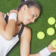 Stock Photo: Portrait of Dreaming Female Tennis Player Lying on Artificial Gr