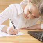 Cute Teenage Girl Writing Her Homework t the Table — Stock Photo #44569341