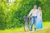 Young Caucasian Couple Having a stroll in Park with Bike — Stock Photo