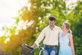 Human Relationships. Happy Couple Outdoors Walking with Bike. — Stock Photo