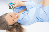 Laughing Expressive Tanned Female Playing with Rubik's Cube Lyin — Foto de Stock