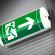 Green emergency exit sign showing the way to escape — Stock Photo