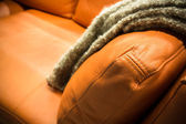Gray blanket draped over a leather couch — Stock Photo