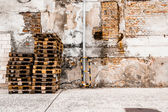 Heap of pallets the brick before a wall — Stok fotoğraf