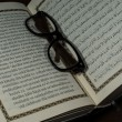Pages of holy koran and geek glasses — Foto Stock
