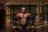 Male bodybuilder resting after doing heavy weight exercise — Stock Photo