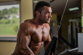 Muscular bodybuilder doing heavy weight exercise for triceps with cable — Stock Photo