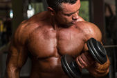 Bodybuilder doing heavy weight exercise for biceps with dumbbell — Stock Photo