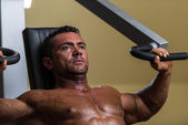 Male bodybuilder doing heavy weight exercise for upper chest — Stock Photo