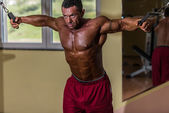 Shirtless body builder doing standing press white cable for chest — Stock Photo