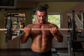 Bodybuilder doing heavy weight exercise for biceps with barbell — Stock Photo