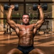 Male bodybuilder doing shoulder press whit dumbbell — Stock Photo