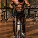 Male bodybuilder using the elliptical machine — Stock Photo