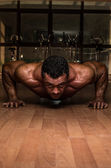 Male bodybuilder doing push ups at the floor — Stock Photo