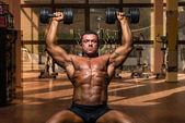 Male bodybuilder doing shoulder press whit dumbbell — Stock Photo