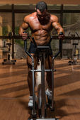 Male bodybuilder using the elliptical machine — Stock Photo
