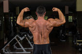 Muscular bodybuilder showing his back double biceps — Stock Photo